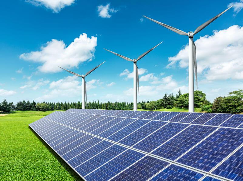 Solar panels and wind turbines in green grass field